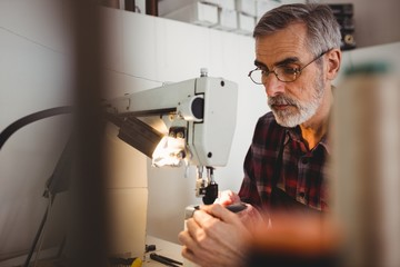 Focus on background of cobbler using sewing machine