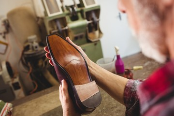Close up of cobbler examining the sole of a shoe