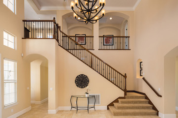 Grant Interior with staircase in large private home with granite floor and large chandelier.