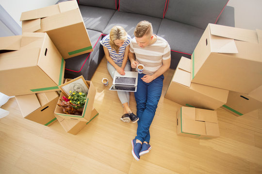 Couple sitting on floor surrounded with moving boxes and using computer