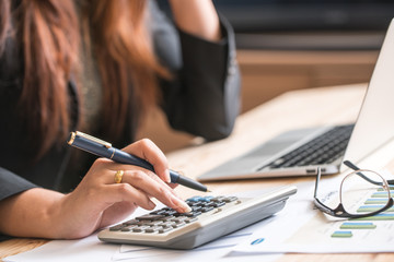 Close up of female accountant or banker making calculations. Sav