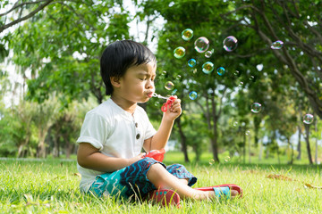 Boy blowing bubbles at the park