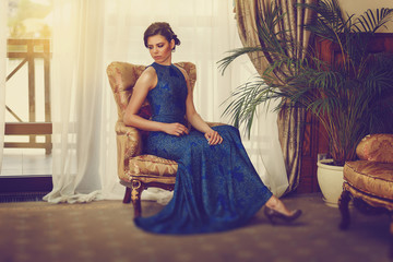 Elegant young woman in evening dress posing in luxury interior. Fashion shot