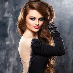 Close-up portrait of sexy young woman in elegant black evening dress with dramatic fashion makeup and hairstyle. Fashion beauty portrait