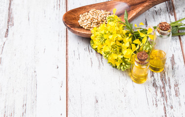 Rape oil and flower on wooden table
