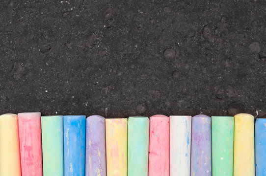 Colorful pastel sidewalk chalk on dark asphalt background.