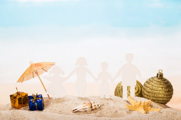 Family of paper, starfish, conch and holiday gifts in sand.