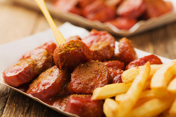 Traditional German currywurst, served with chips on disposable p