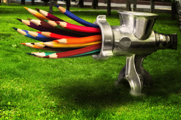 Obraz Photo merge  - meat grinder grinds colored pencils on a green lawn. - fototapety do salonu