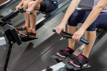 Mid section of people exercising on rowing machine