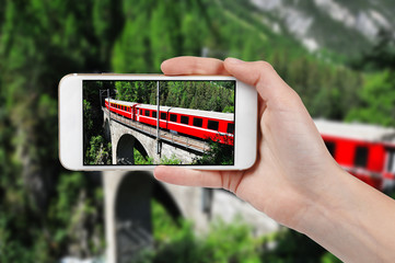Taking photo of red train on viaduct with a phone