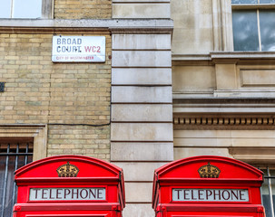 Iconic red telephone booths and street sign on Broad Court, Covent Garden, London