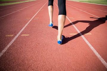Female athlete feet running on the running track