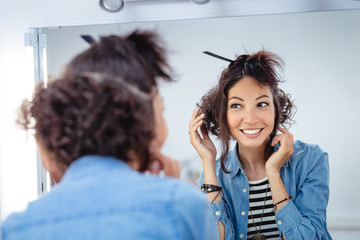 A young woman checks and corrects her hair in the mirror