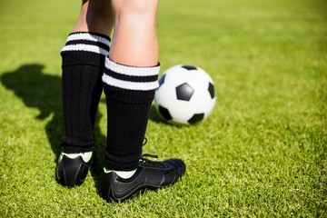 Feet of a female football player and a ball