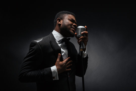Afro amerian man singing into vintage microphone