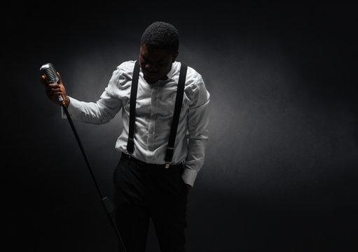 Male singer posing over dark background