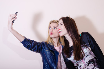 portrait of 2 young attractive adorable women happy smiling having fun friendly hugging and making selfie on light copy space background