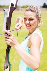Happy female athlete practicing archery