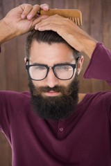 Hipster man using a comb