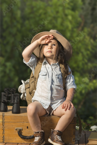 2440de5f84cba Adorable little girl in a safari hat and explorer clothes playing safari  sitting on wooden suitcase outdoor. Children s play concept.