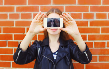 Fashion woman makes self portrait on smartphone view of screen o