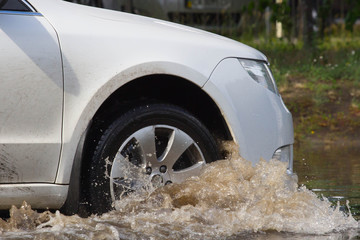 cars driving on a flooded road during a flood caused after heavy rain