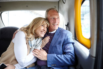 Mature romantic dating couple en route in black cab backseat
