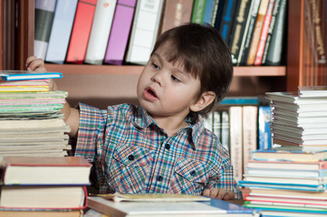 The child sits at a table with books