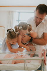 Father and children looking at new baby in hospital
