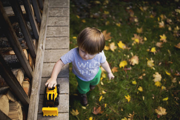 Toddler Pushing Yellow Tractor in the Fall
