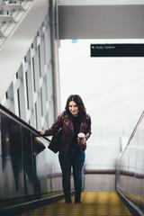 Woman with Coffee on Escalator