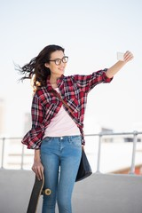 Hipster with skateboard taking pictures