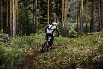 rider on a bicycle coming down mountain during downhill competition
