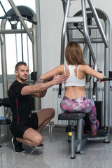 Woman Train Back On Machine With Personal Trainer