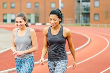 Two young women walking along running track