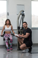 Trainer Writing On Clipboard While Woman Training Triceps