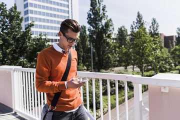 Young man on bridge looking at cell phone