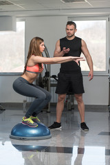Personal Trainer Helping Woman On Bosu Balance Ball