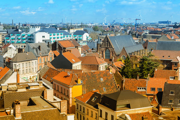 Aerial panoramic view of Ghent, Belgium with  roofs and traditional medieval buildings, church against cloudy blue sky