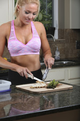 Fit and attractive young woman preparing healthy meal on a cutting board