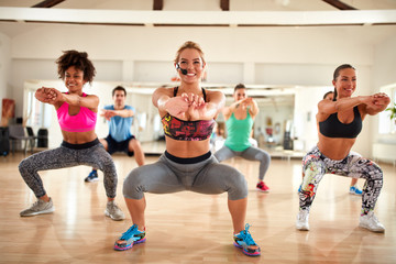 Female instructor doing exercises for shaping breech and thighs