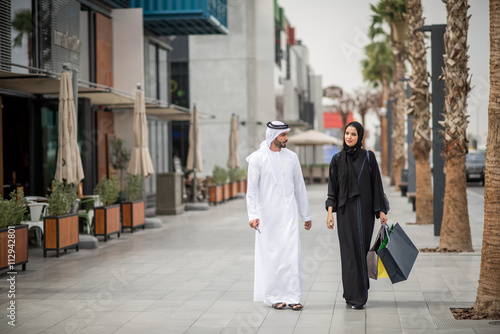 10c7d1b26d831 Middle eastern shopping couple wearing traditional clothing carrying  shopping bags, Dubai, United Arab Emirates