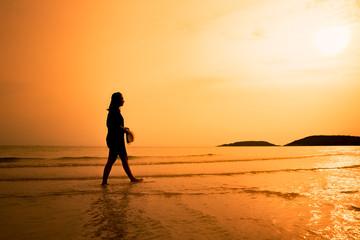 Silhouette happy woman walking on beach, Happy young woman walki