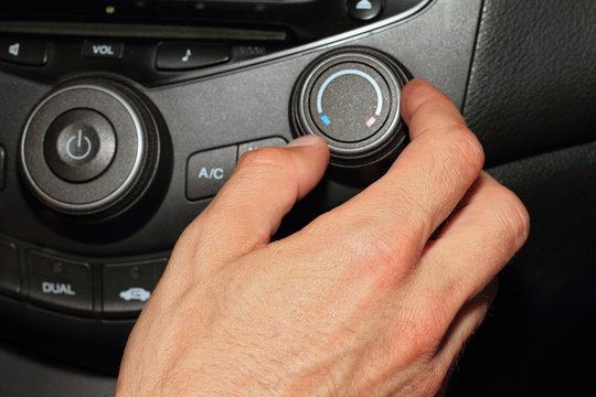 Car air conditioner service. Vehicle interior with visible climate controls, fragment of instrument panel