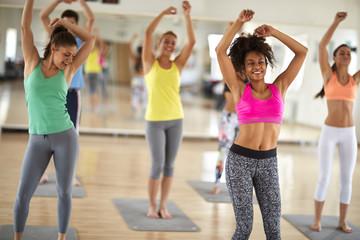 Cheerful women dance at gym