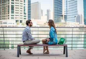 Tourist couple sitting on waterfront talking, Dubai, United Arab Emirates