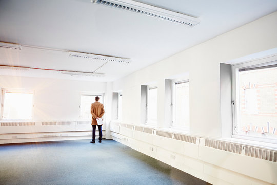 Rear view of man in empty office, hands behind back looking out of window