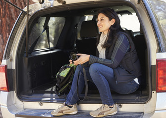 Woman holding camera sits in the open back of a car