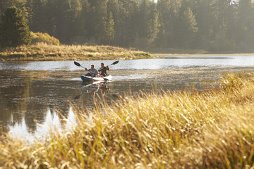 Two young men kayaking on a lake, tall grass in foreground